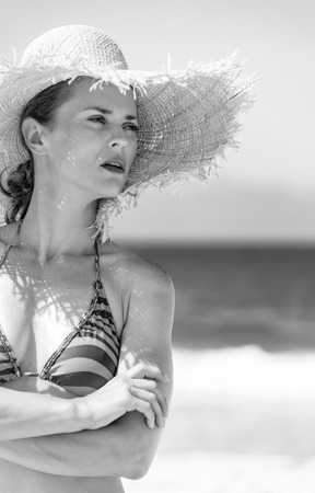 Blue sea, white sand paradise. Portrait of young woman in beachwear and straw hat on the seashore looking into the distance