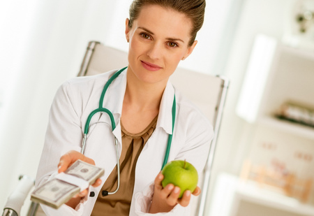 Doctor woman showing apple and pack of money Stock Photo