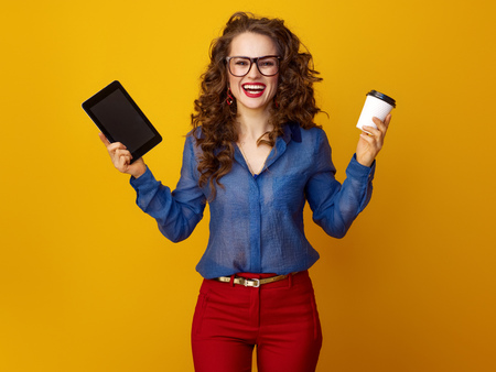 Portrait of happy young woman with long wavy brunette hair showing a coffee cup and tablet PC isolated on yellow Stock Photo