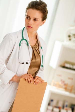 Thoughtful medical doctor woman with clipboard