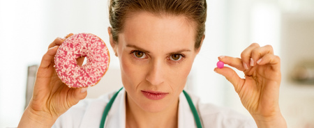 Serious medical doctor woman showing donut and pill