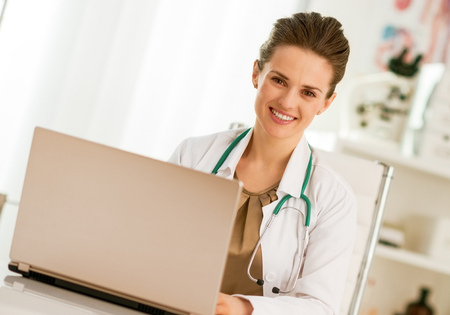 Happy medical doctor woman working on laptop Stock Photo