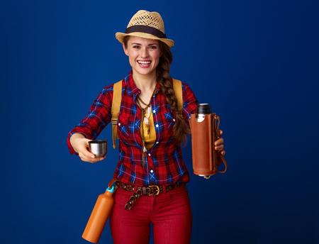 感動的な場所を探しています。青に隔離された魔法瓶から熱い飲み物を提案するチェック柄のシャツを着た活発な女性ハイカーの笑顔 写真素材