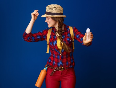 Searching for inspiring places. happy healthy traveller woman in a plaid shirt showing antiperspirant against blue background Stock Photo