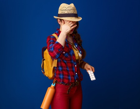 Searching for inspiring places. ill woman hiker with backpack with pills in a blister pack experience pain on blue background Stock Photo