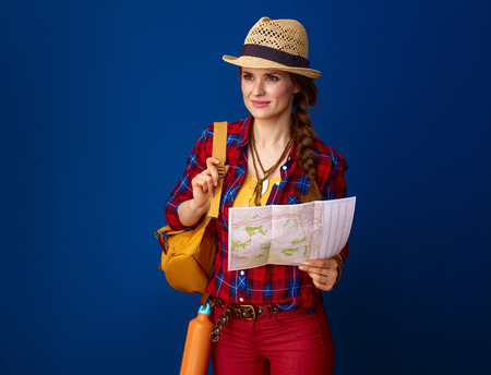 Searching for inspiring places. smiling adventure traveller woman with backpack and map looking into the distance isolated on blue