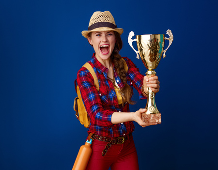 Searching for inspiring places. young excited woman hiker in a plaid shirt showing goblet isolated on blue