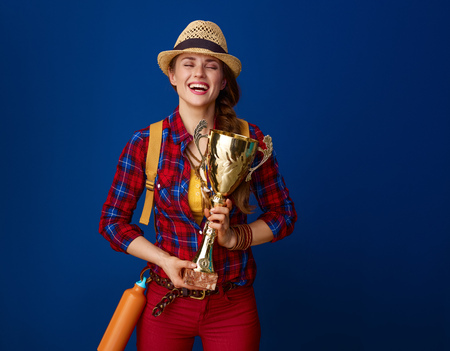 Searching for inspiring places. smiling young woman hiker with backpack hugging goblet against blue background Stock Photo