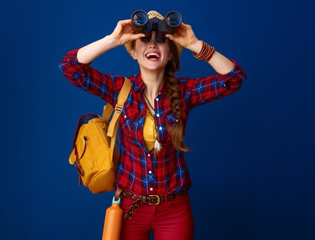 Searching for inspiring places. happy fit tourist woman with backpack looking up through binoculars on blue background