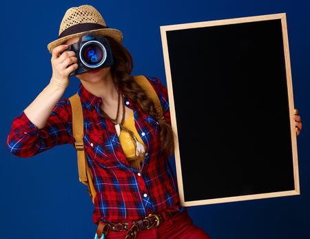Searching for inspiring places. healthy traveller woman in a plaid shirt with blackboard and digital camera taking photo isolated on blue background