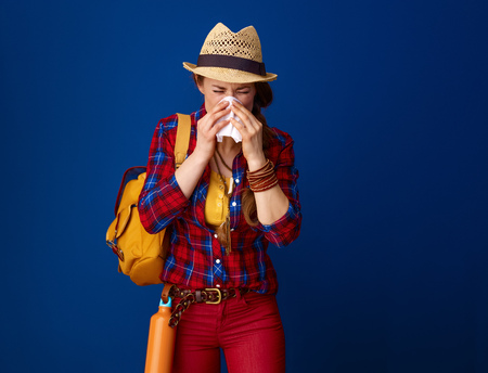 Searching for inspiring places. ill traveller woman in a plaid shirt blowing nose against blue background Stock Photo