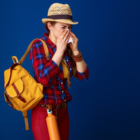 Searching for inspiring places. ill woman hiker in a plaid shirt blowing nose isolated on blue background