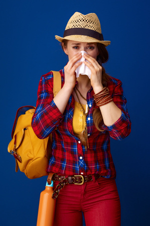 Searching for inspiring places. ill woman hiker in a plaid shirt blowing nose isolated on blue Stock Photo