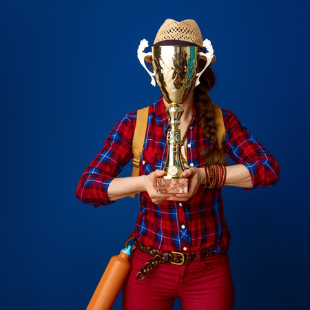 Searching for inspiring places. adventure traveller woman in a plaid shirt hiding behind goblet on blue background