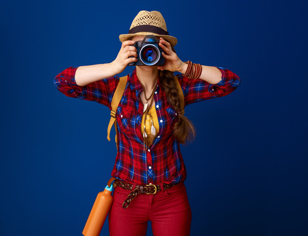 Searching for inspiring places. adventure traveller woman in a plaid shirt with digital camera taking photo on blue background Stock Photo