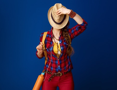 Searching for inspiring places. fit woman hiker with backpack and headphones listening to the music hiding behind hat against blue background