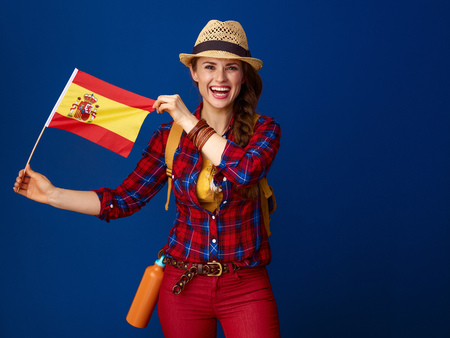 Searching for inspiring places. smiling healthy traveller woman in a plaid shirt showing the flag of Spain against blue background Stock fotó - 98714381