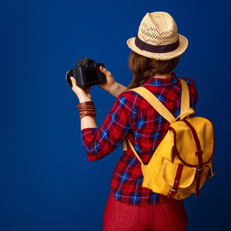 Searching for inspiring places. Seen from behind healthy tourist woman with backpack and DSLR camera taking photo on blue background