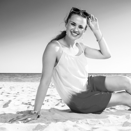 Colorful and wonderfully cheerful mood. smiling trendy woman in colorful dress sitting on the beach