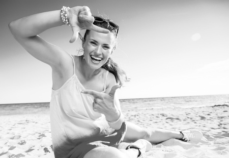 Colorful and wonderfully cheerful mood. happy modern woman in colorful dress on the beach with hands framing