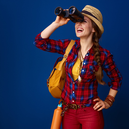 Searching for inspiring places. happy active woman hiker with backpack looking into the distance through binoculars against blue background