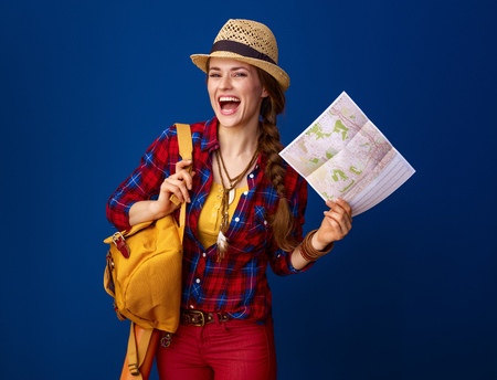 Searching for inspiring places. happy healthy traveller woman with backpack and map isolated on blue background 스톡 콘텐츠