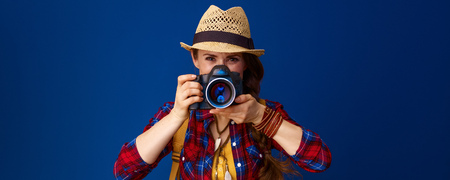 Searching for inspiring places. young traveller woman in a plaid shirt with digital camera taking photo against blue background