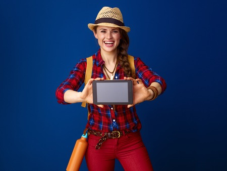 Searching for inspiring places. happy active woman hiker in a plaid shirt showing tablet PC blank screen isolated on blue Stock Photo