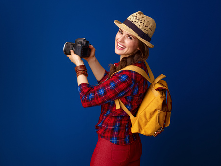 Searching for inspiring places. smiling young woman hiker in a plaid shirt with modern DSLR camera taking photo against blue background