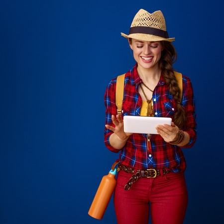 Searching for inspiring places. smiling active tourist woman in a plaid shirt using tablet PC isolated on blue background