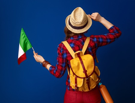 Searching for inspiring places. Seen from behind young woman hiker with backpack and the flag of Italy isolated on blue Stock Photo