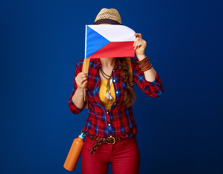 Searching for inspiring places. active woman hiker with backpack hiding behind the flag of Czech isolated on blue background Standard-Bild - 98722907
