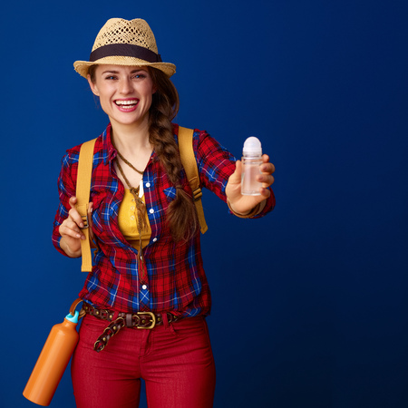 Searching for inspiring places. happy healthy tourist woman in a plaid shirt showing antiperspirant on blue background