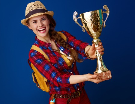 Searching for inspiring places. happy active traveller woman in a plaid shirt showing goblet on blue background