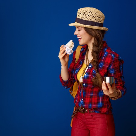 Searching for inspiring places. smiling fit traveller woman with backpack eating a sandwich and drinking hot beverage on blue background Foto de archivo - 98729709