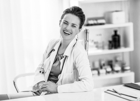 Portrait of laughing medical doctor woman sitting in office
