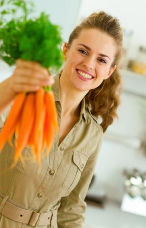 Happy young housewife giving bunch of carrots Banco de Imagens