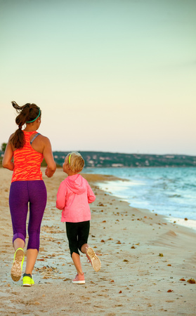 Look Good and feel great. Seen from behind young mother and daughter in sport style clothes on the seacoast in the evening jogging