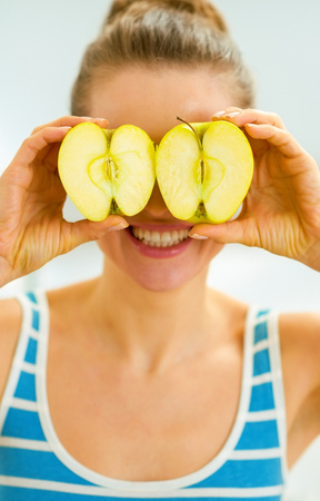 Happy young woman holding two slices of apple in front of eyes