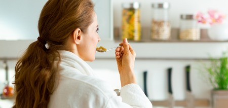 Young woman in bathrobe eating breakfast. rear view Stock Photo