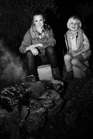 Into the wild. smiling young mother and daughter travellers sitting near the camping fire
