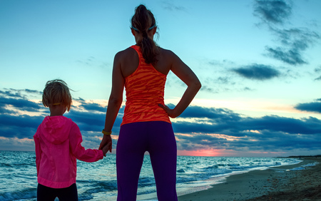 Look Good and feel great. Silhouette. Seen from behind active mother and child in sport style clothes on the seacoast on the sunset looking into the distance 版權商用圖片