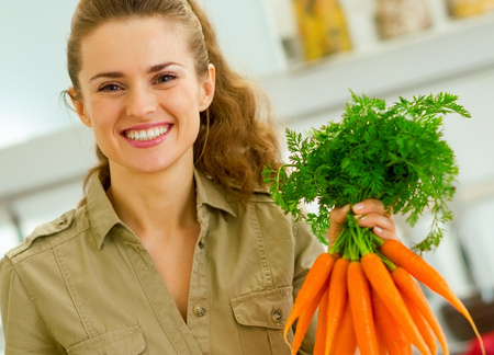 Happy young housewife holding bunch of carrots in kitchen Banco de Imagens