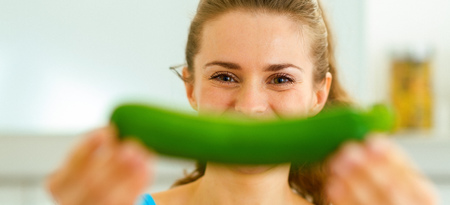 Young woman smiling with zucchini