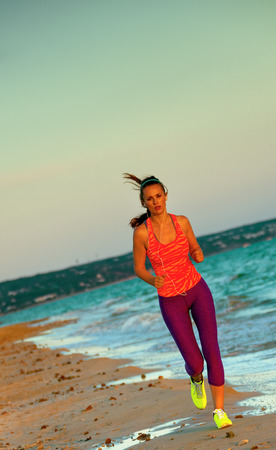 Look Good and feel great. healthy fit woman in sport style clothes on the seashore in the evening running