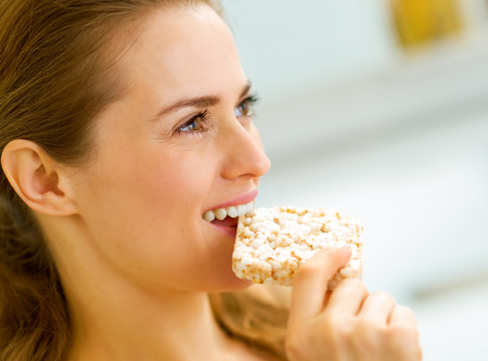 young woman eating crisp bread in kitchen Stockfoto