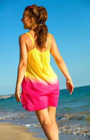 Colorful and wonderfully cheerful mood. Seen from behind relaxed healthy woman in colorful dress on the seacoast in the evening Stock Photo