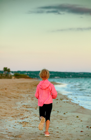 Look Good and feel great. Seen from behind healthy child in sport style clothes on the seashore in the evening running Stock Photo