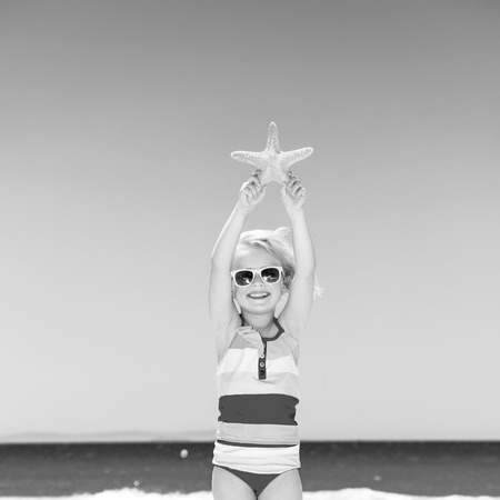 sea, white sand paradise. happy modern child in swimsuit on the seacoast showing starfish Stock Photo