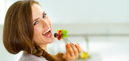 Smiling young woman eating fresh salad in modern kitchen Stok Fotoğraf